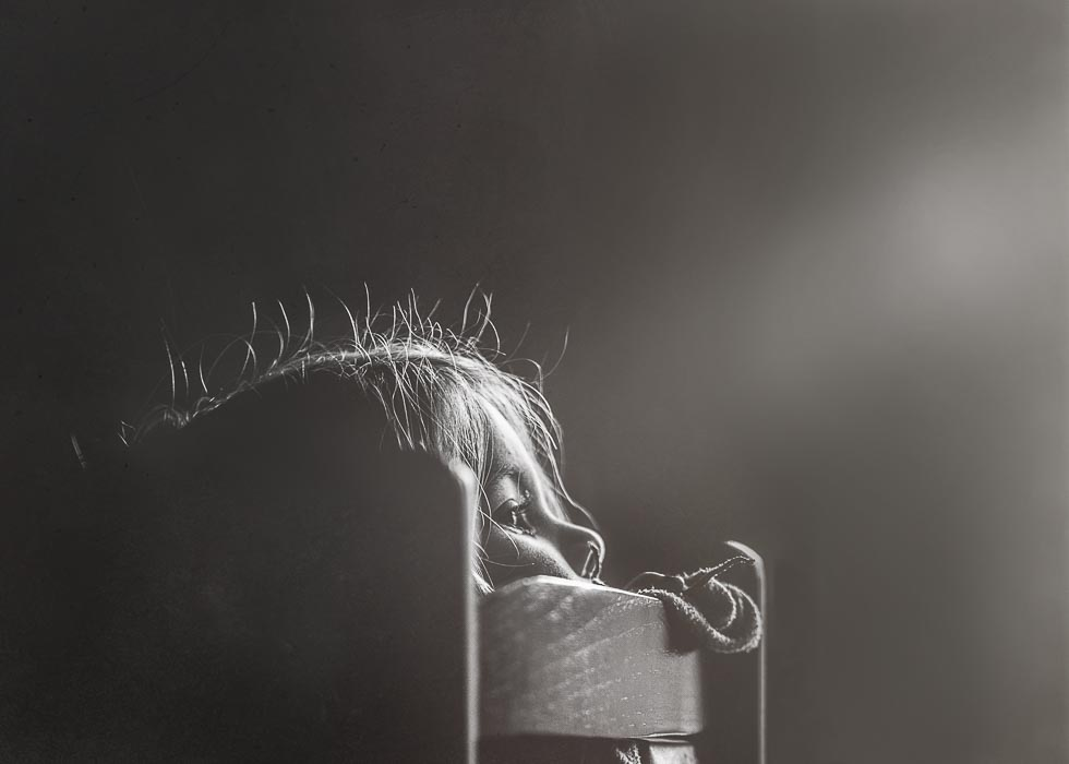 Black and white image of a small girl peering over the back of a wooden rocking chair with sun rays on her face and rim lighting on her profile and hair.