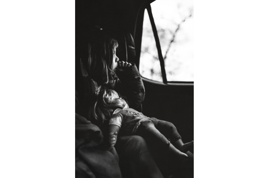 Black and white images of four year old girl in her car seat holding her doll and looking out the window pensively.
