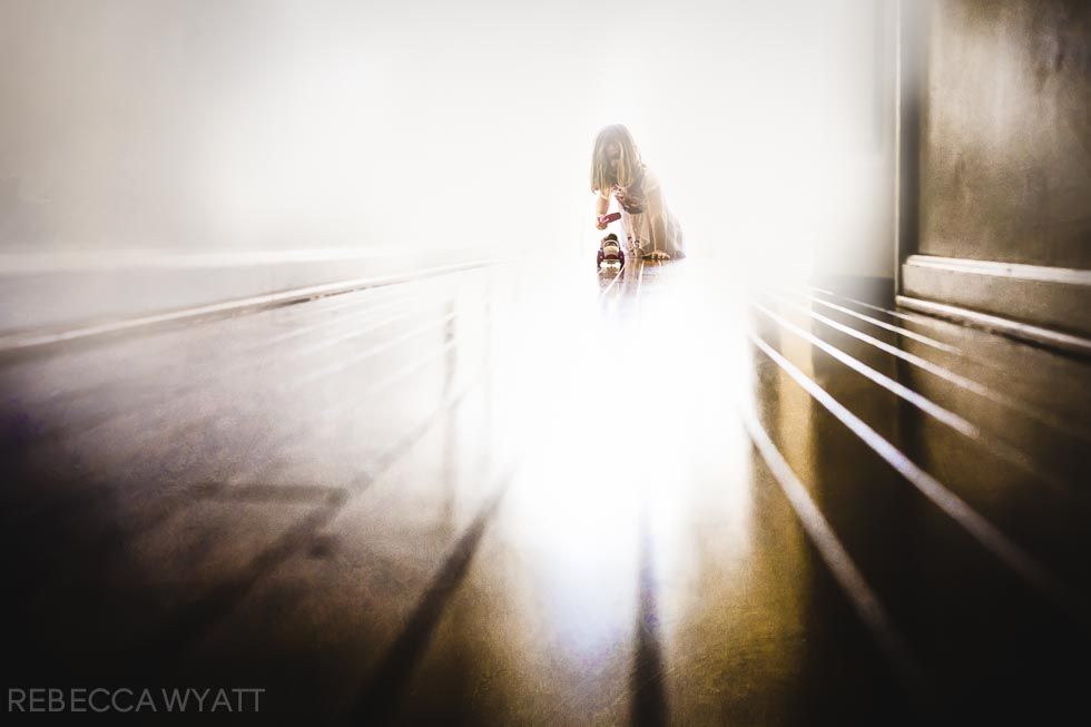 Artistic photograph of girl playing with her remote control car on a long wooden floor.