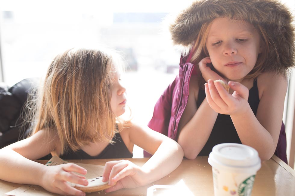 Two young girls sitting in Starbucks sharing hot chocolate and a cookie.