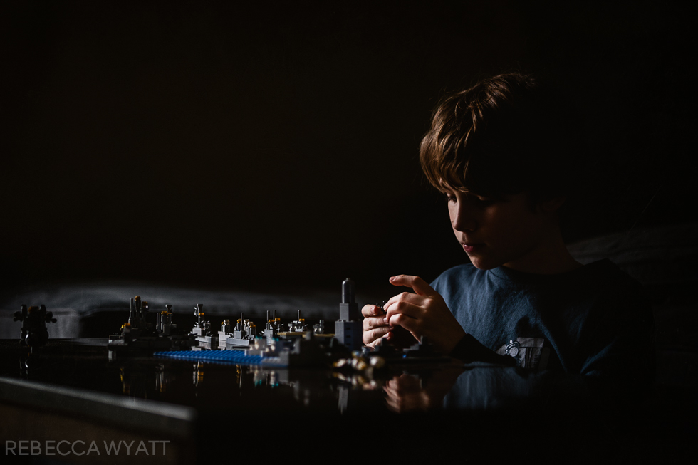 color photograph of boy side lit dramatically  while playing legos