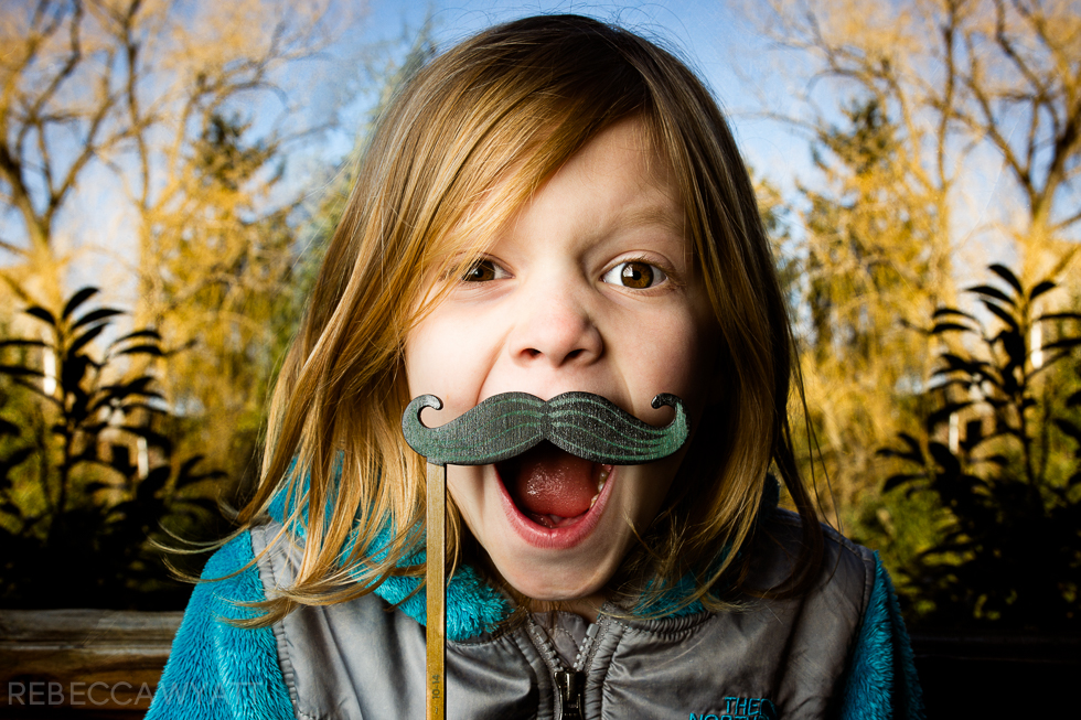 Off Camera Flash Image of young girl in color holding mustache prop
