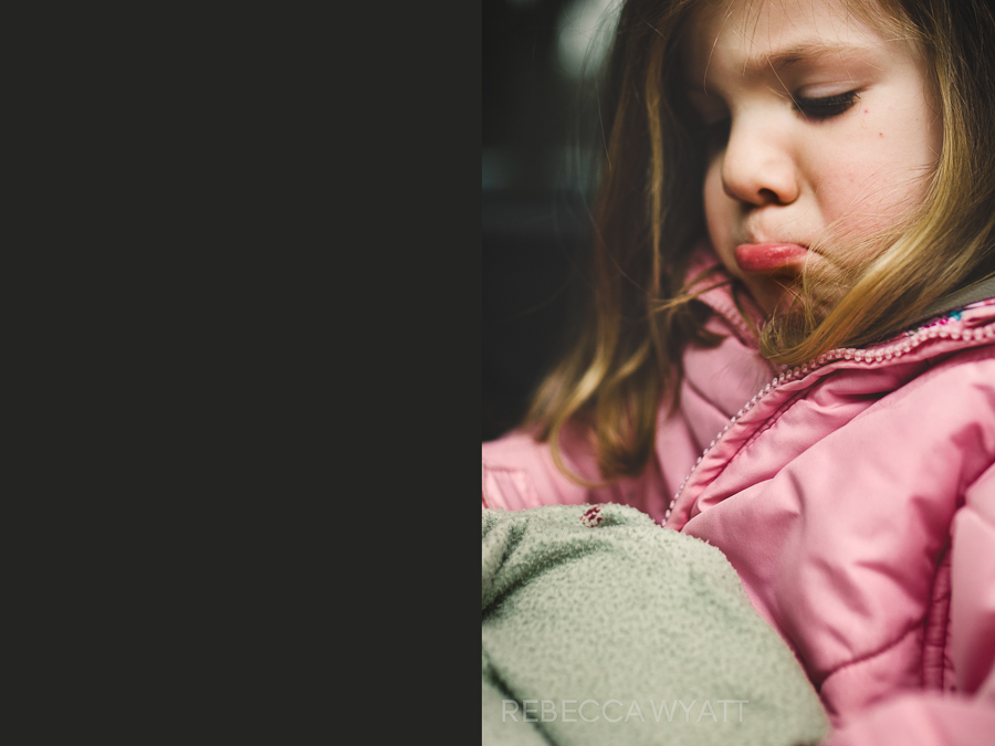 Girl in pink coat sitting in car seat pouting with her lower lip.