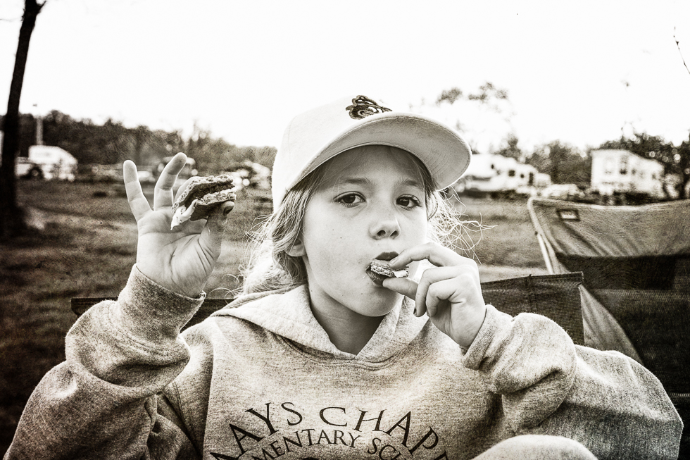 black and white photograph of a girl eating s'mores on a camping trip