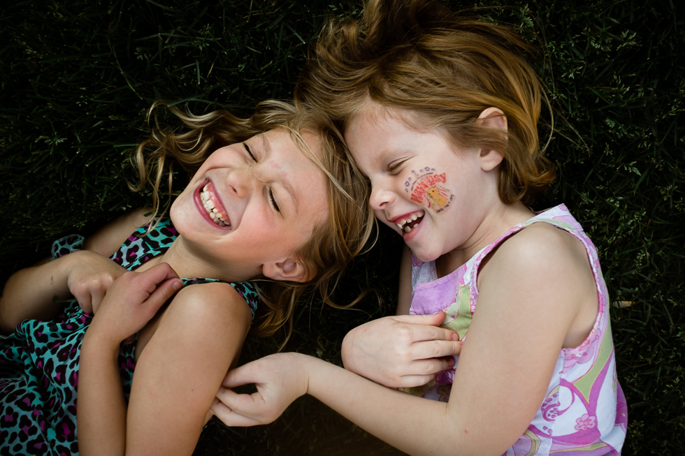 Girl cousins tickling each other in the grass