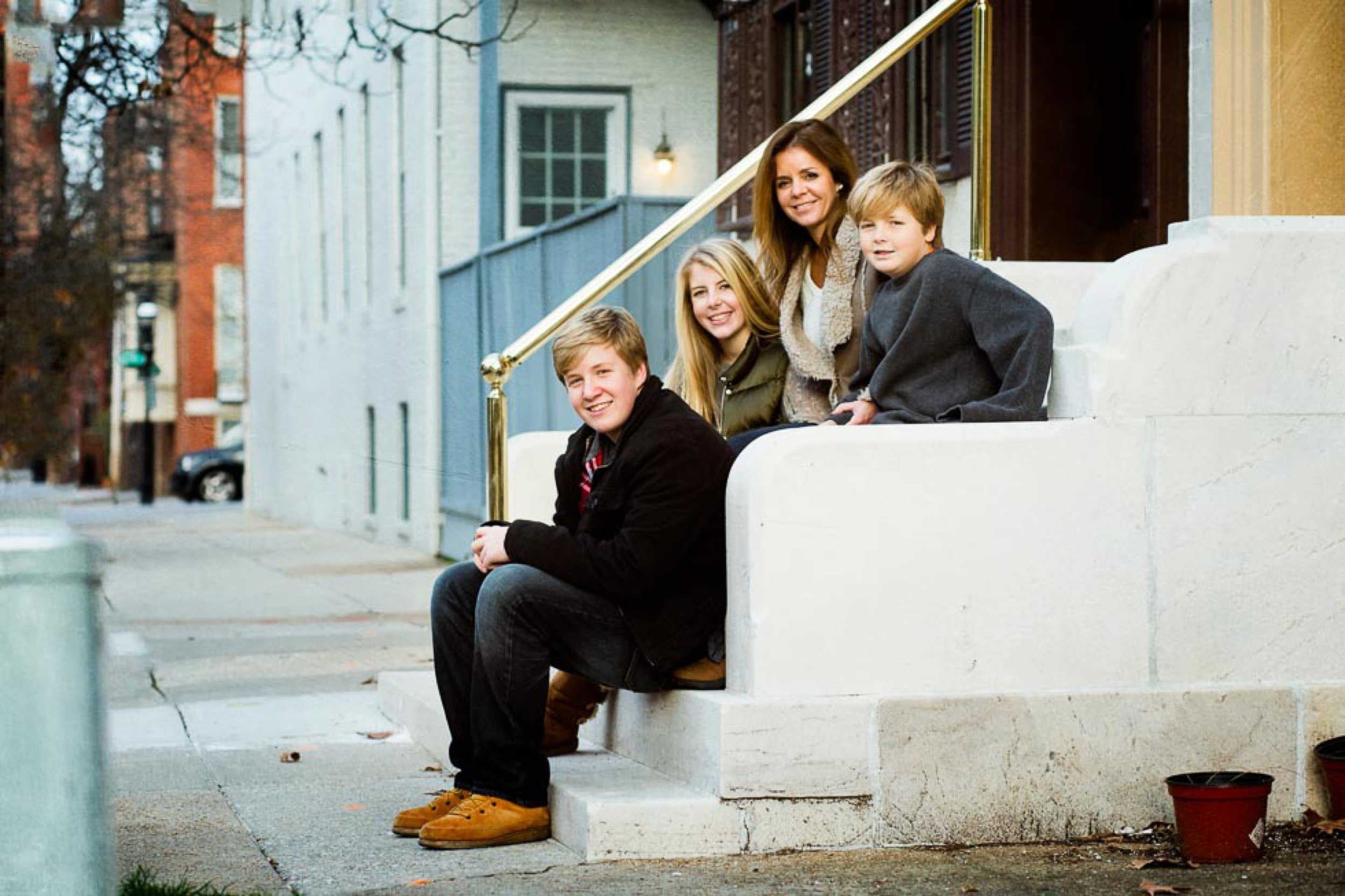 Mom sitting with her three awesome kids on a stoop.
