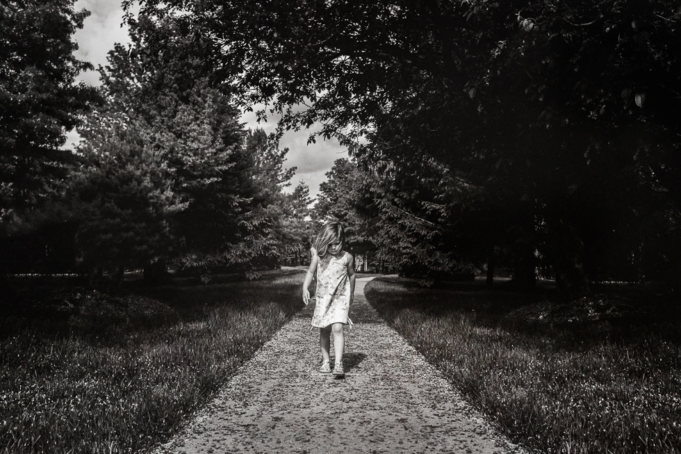 Black and white image of young girl walking on sidewalk.
