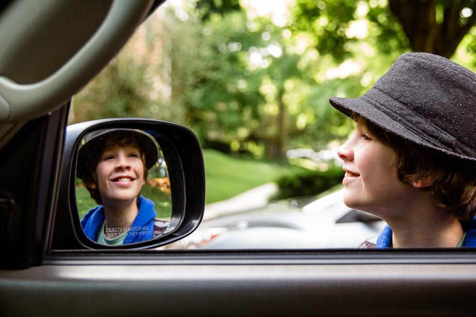 Boy looking in side view mirror wearing fedora