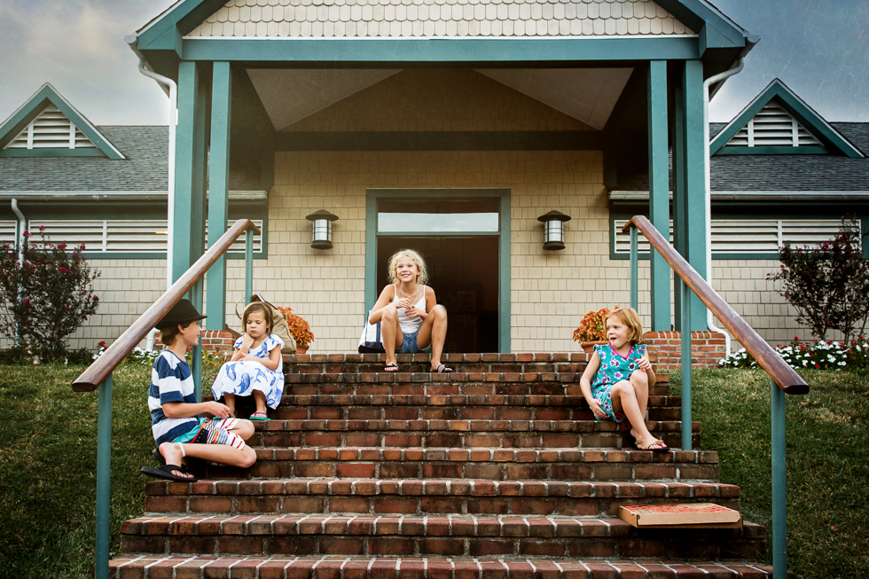 four siblings sitting on steps to pool