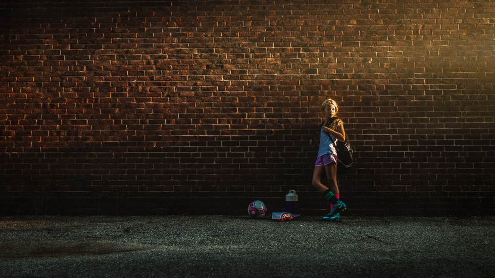 soccer player against wall in evening light