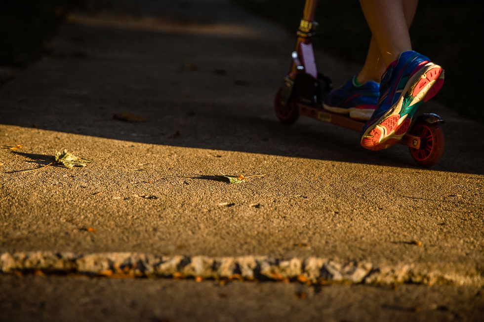 evening light on a side walk with a child scootering