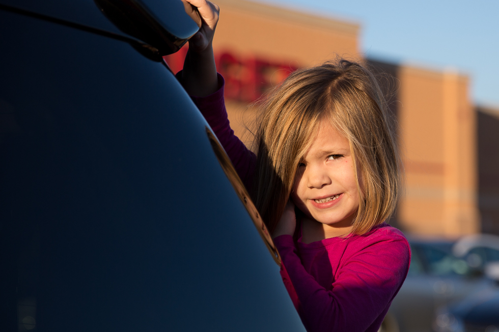 Four year old child hanging off the back of mom's car in Target parking lot.
