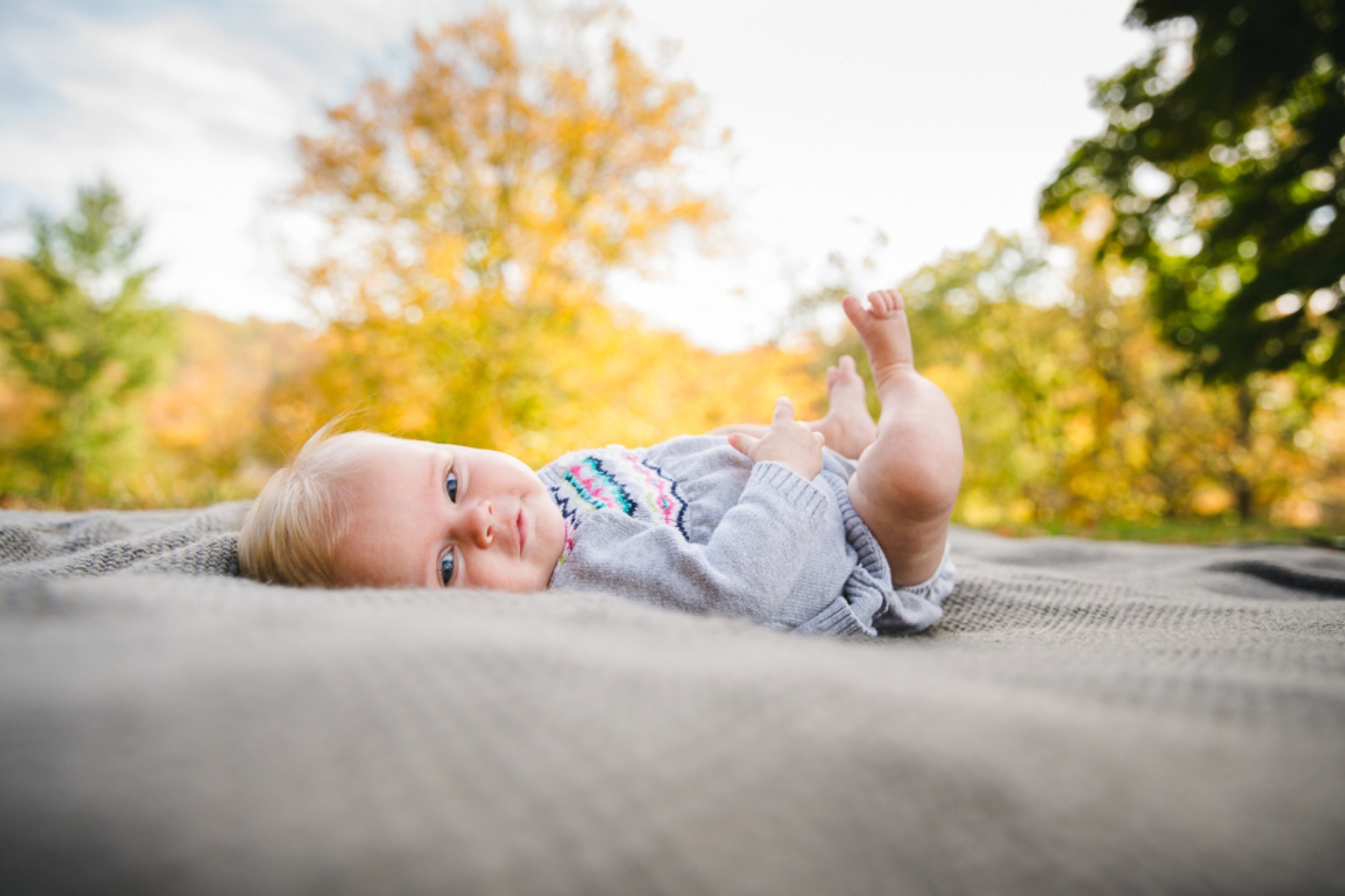 sweet blue eyed baby laying on a gray blanket amidst fall foliage.