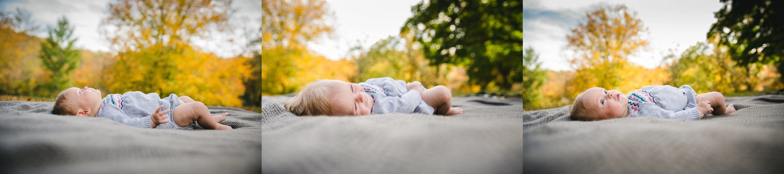 lovely baby exploring the beautiful environment of a baltimore park while lying on the ground