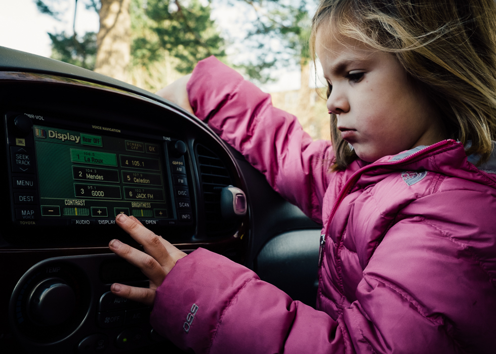 girl paying with radio in front seat of the car with air blowing through her hair