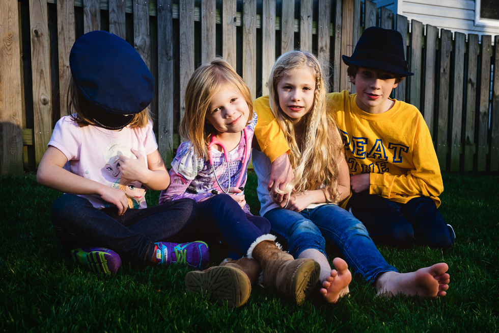 four cute kids sitting by a fence together