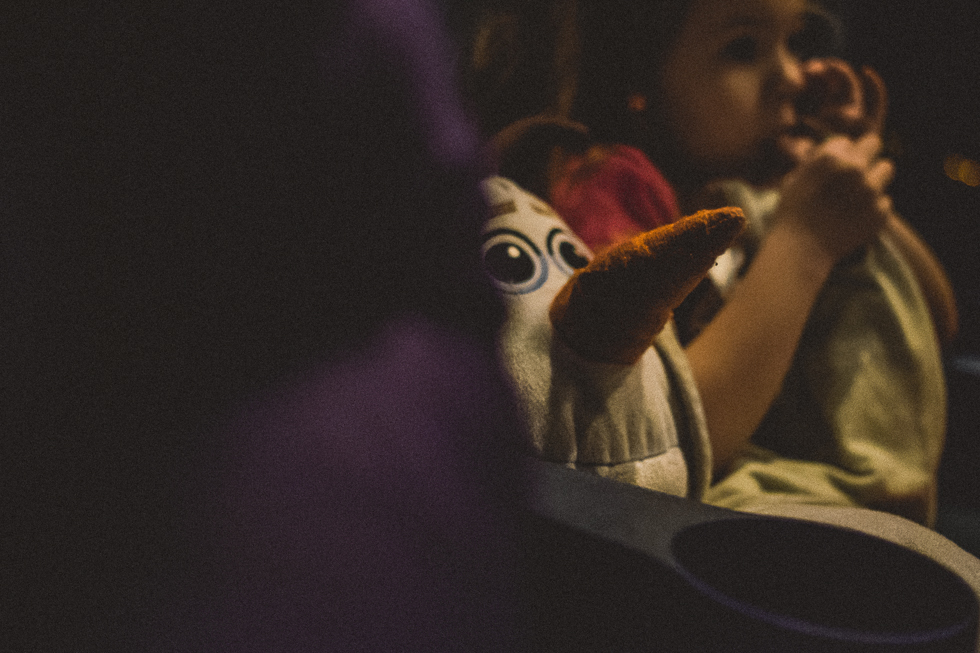 girl and stuffed olaf sitting in the movie theater.