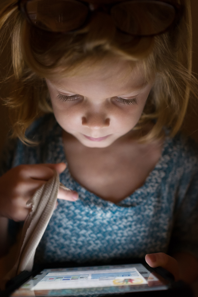 girl in blue sweater looking down at a iPad