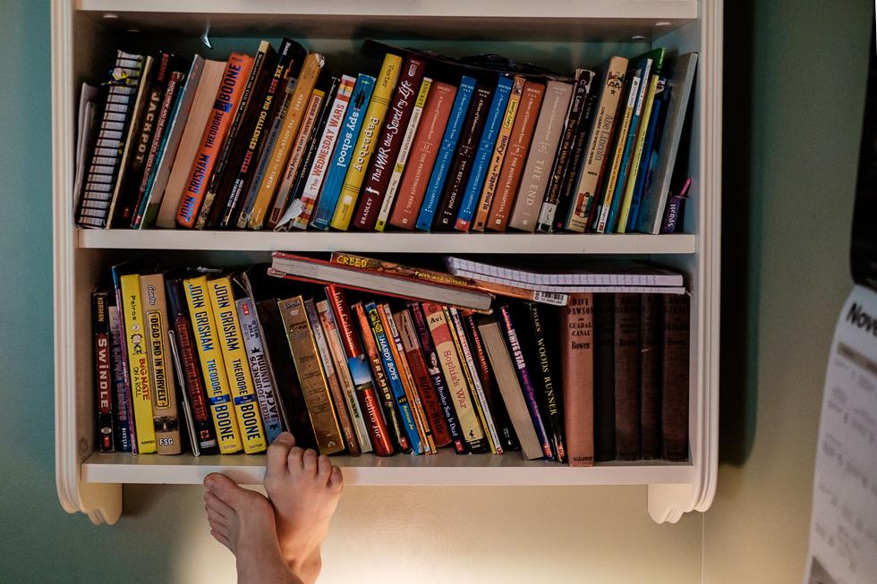 boy resting his feet upon wall bookshelf