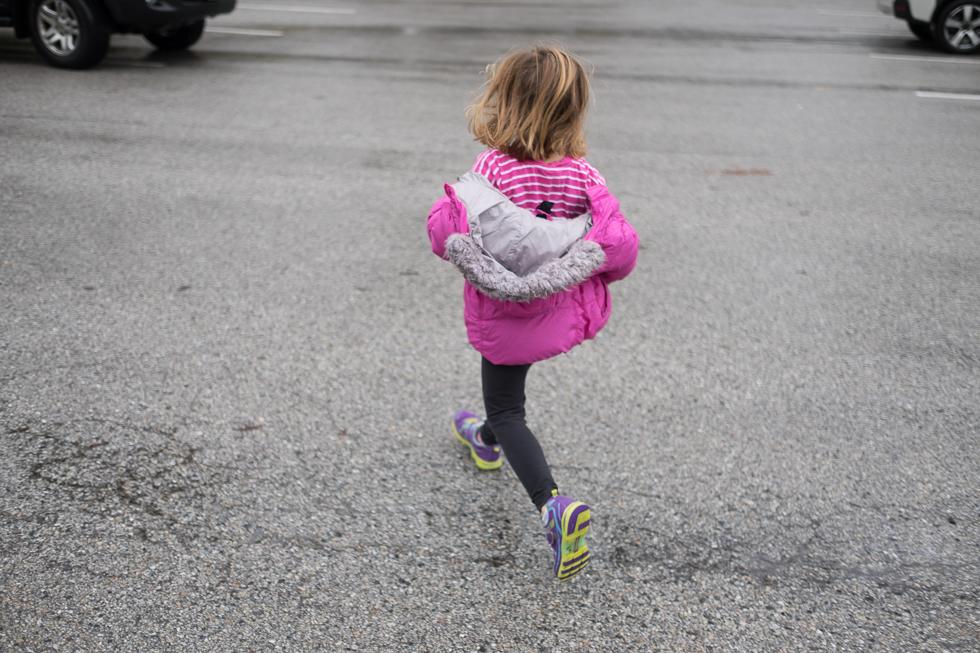 child in purple jacket running across parking lot in the rain