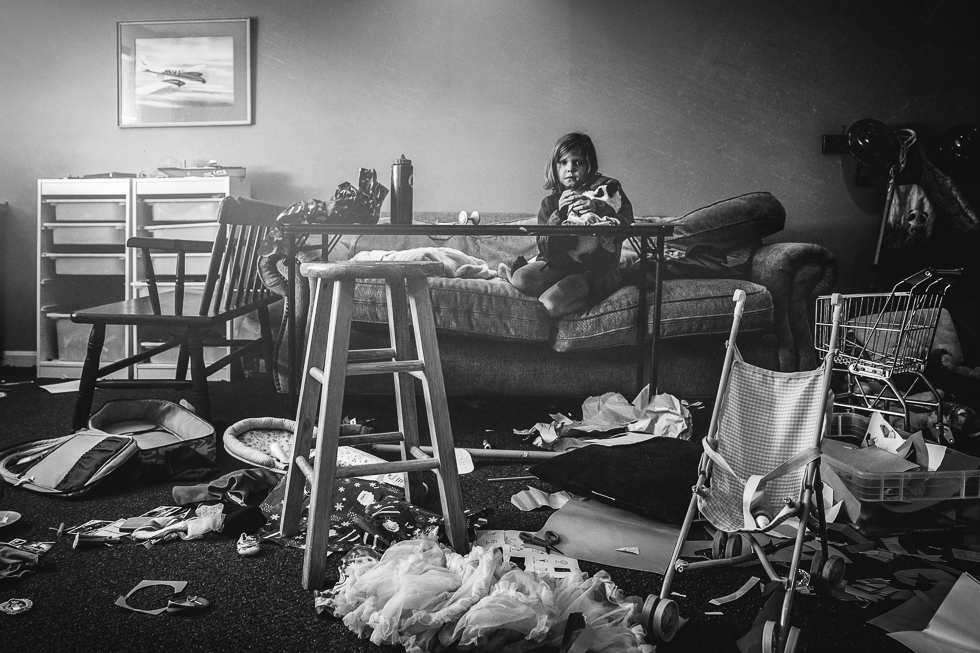 girl sitting in very messy playroom in a black and white photograph