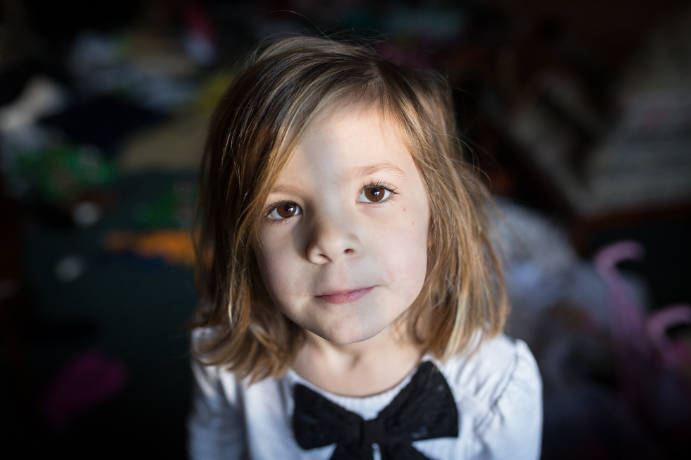 cute girl in white shirt with black bow looking at the camera with an abstract mess on the floor behind her.