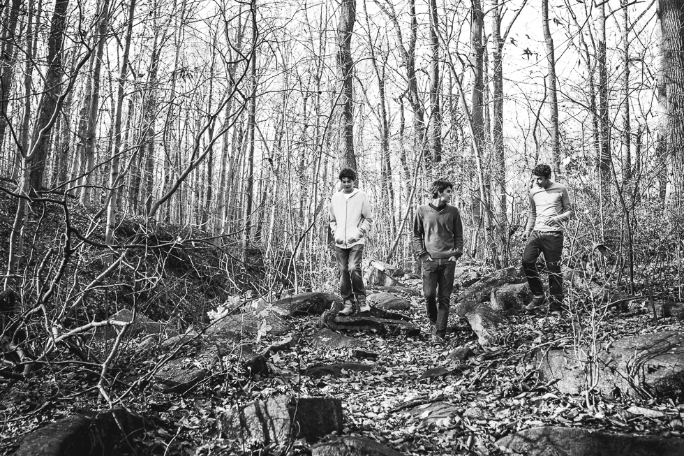 Copy of Black and white family photo of three sons walking through the woods.