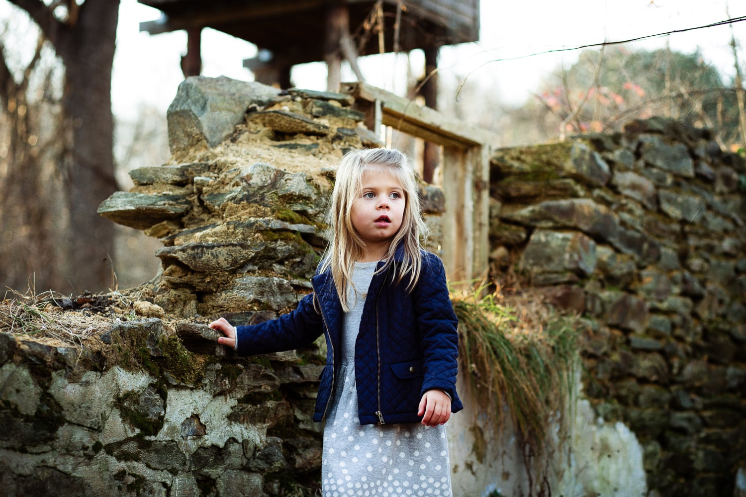 adorable blonde child exploring old stone structure with her family.