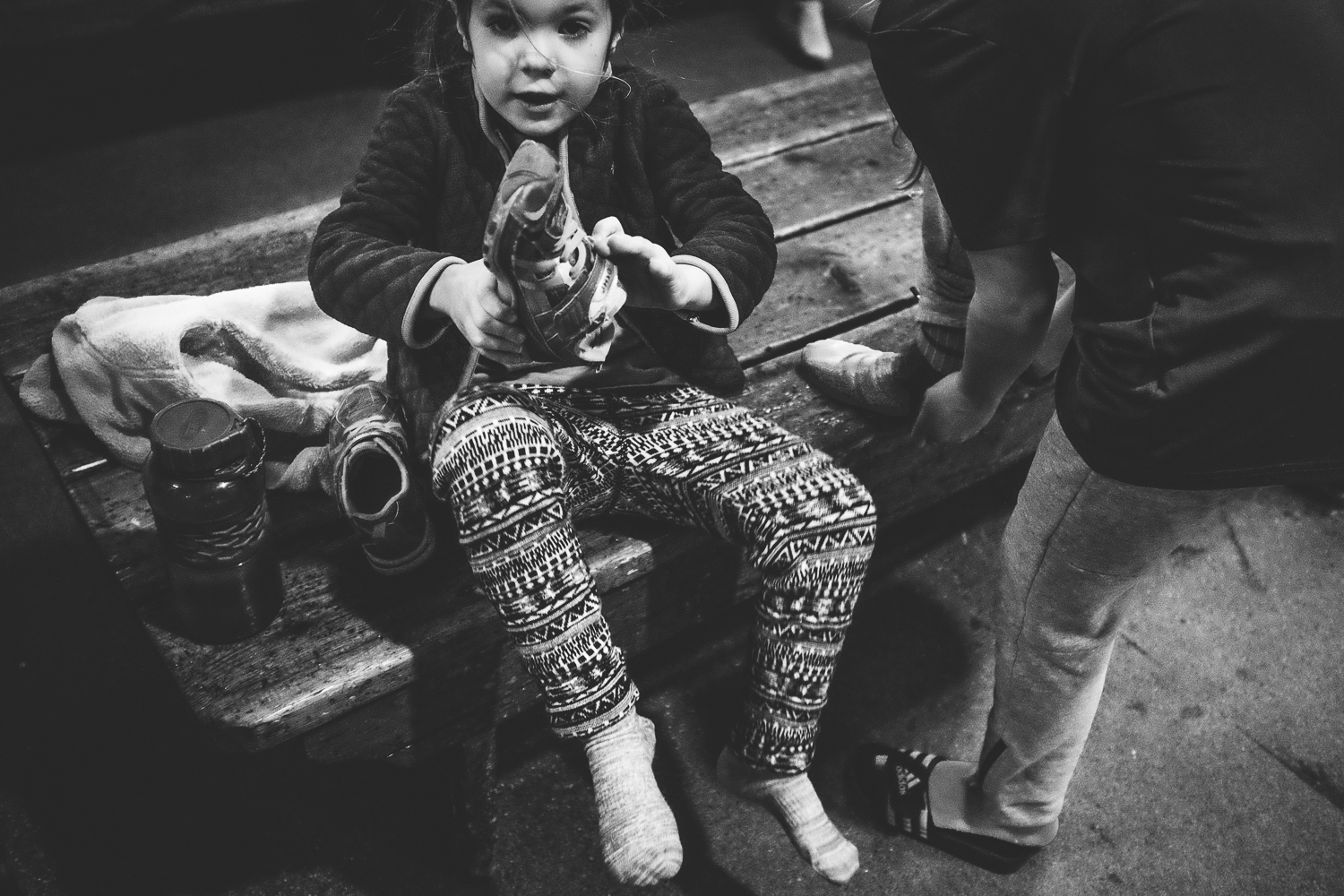 young child putting on her shoes after removing her skates