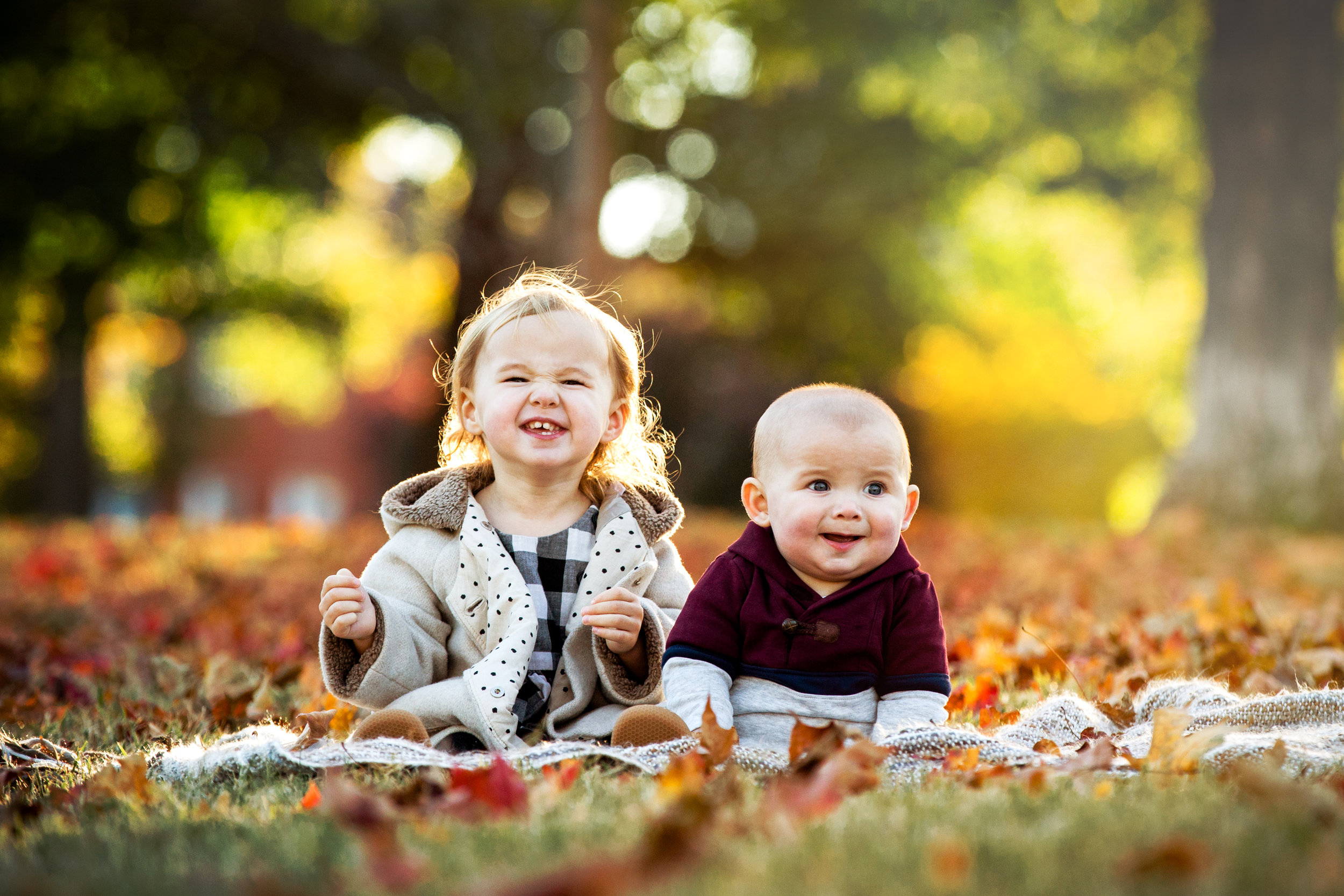 sister and baby brother smile while seated on camera in family sibling portrait