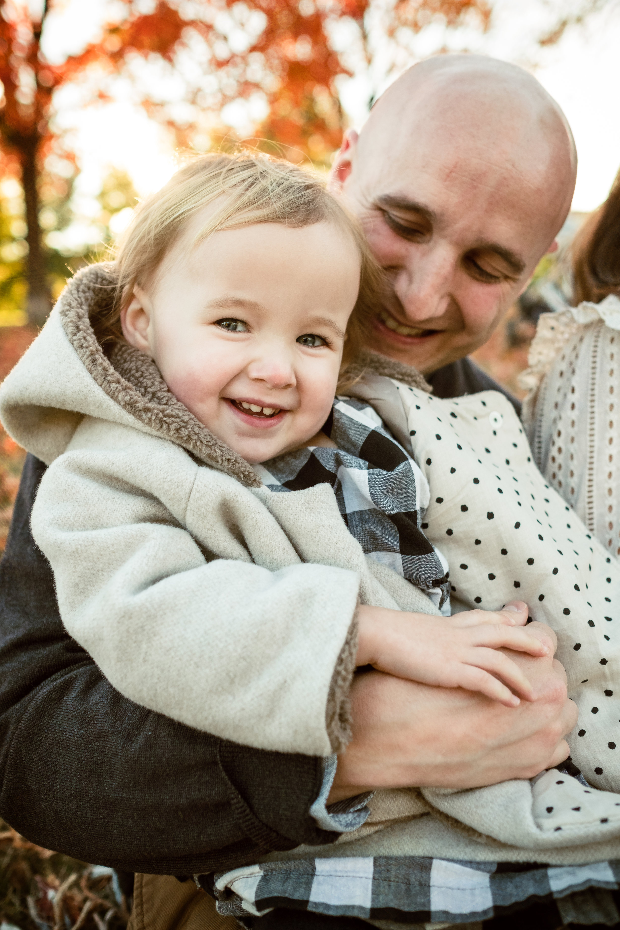 smiling toddler girl snuggles in adoring father's lap