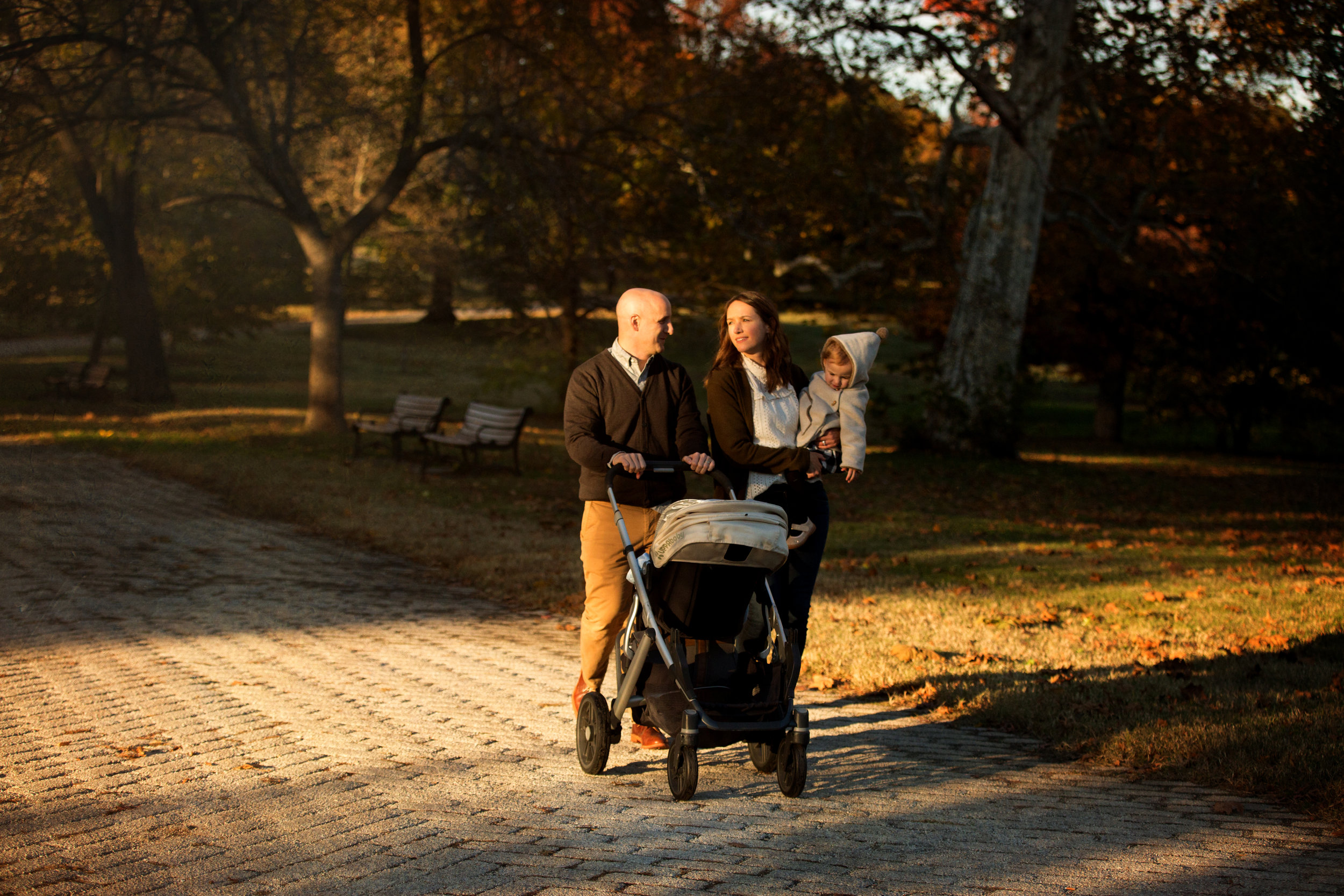 parents and children walking with stroller in evening with sunlight on sidewalk