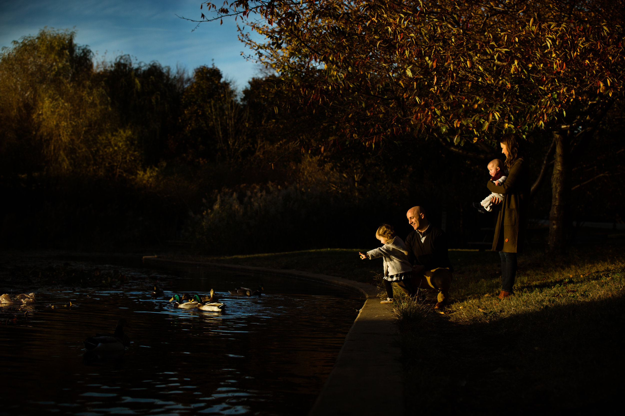 dad helps daughter feed the ducks in Patterson Park, Baltimore while mother holding baby son look on
