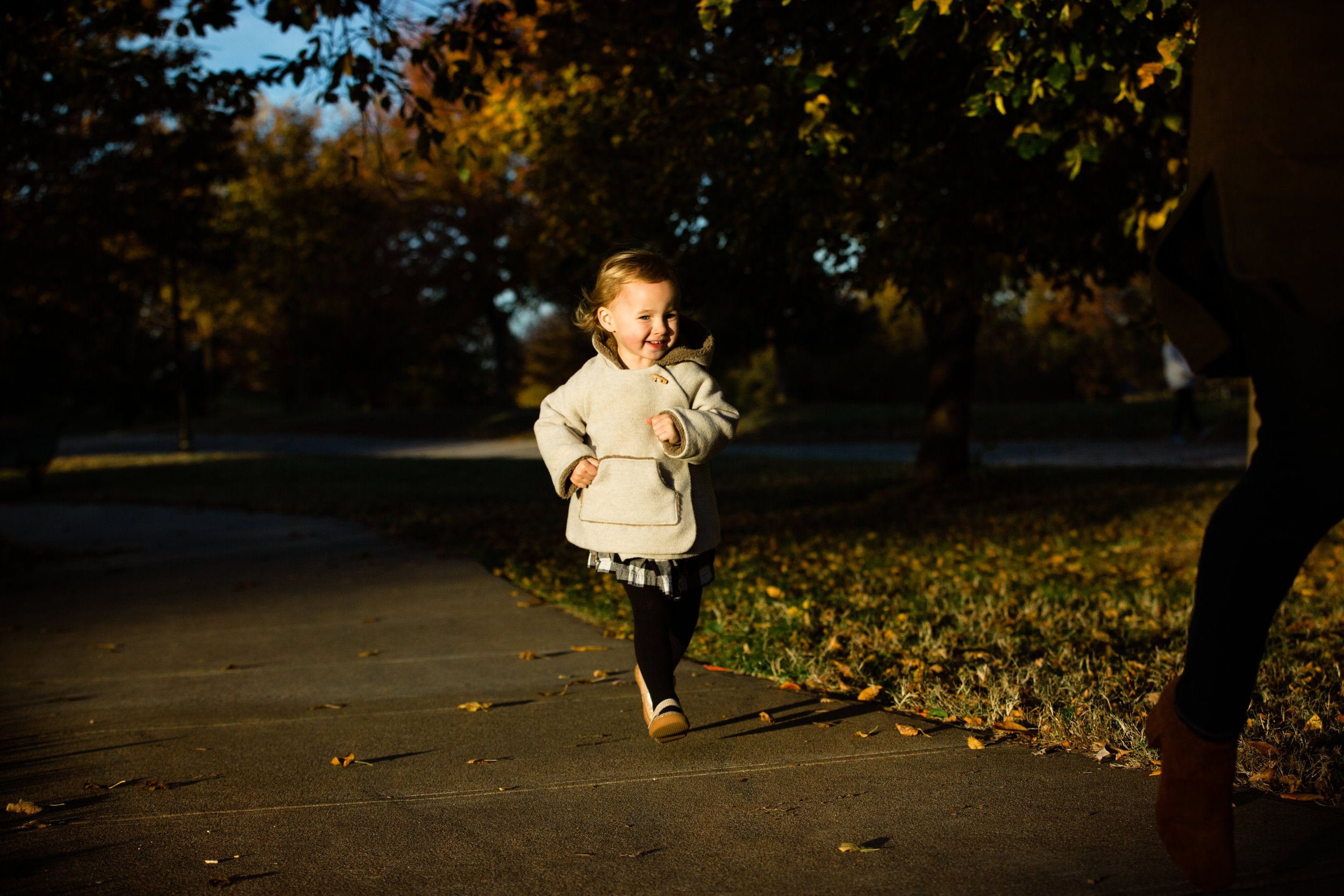 little girl runs along park path with big smile