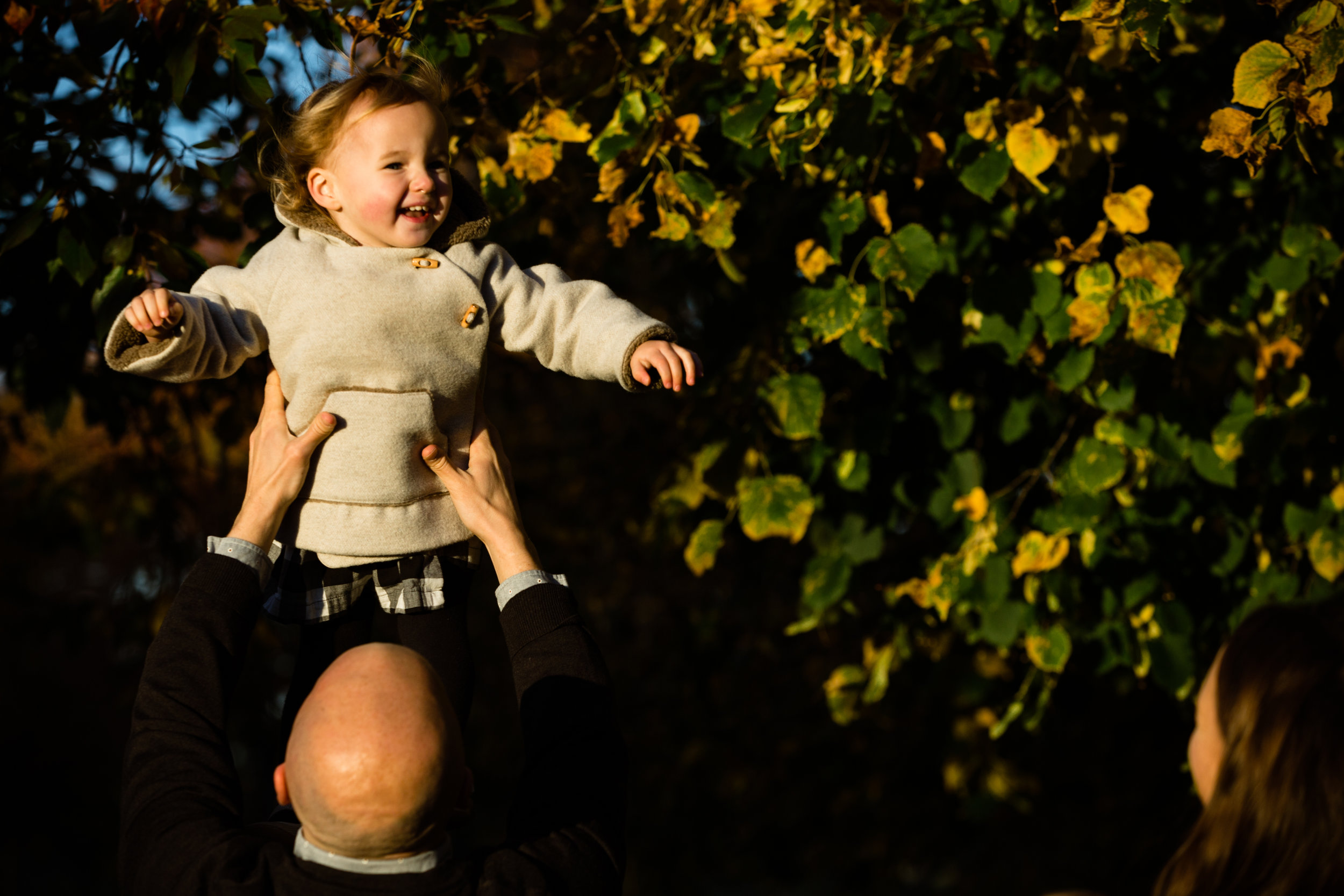 father holds sun lit daughter up in the air in photograph