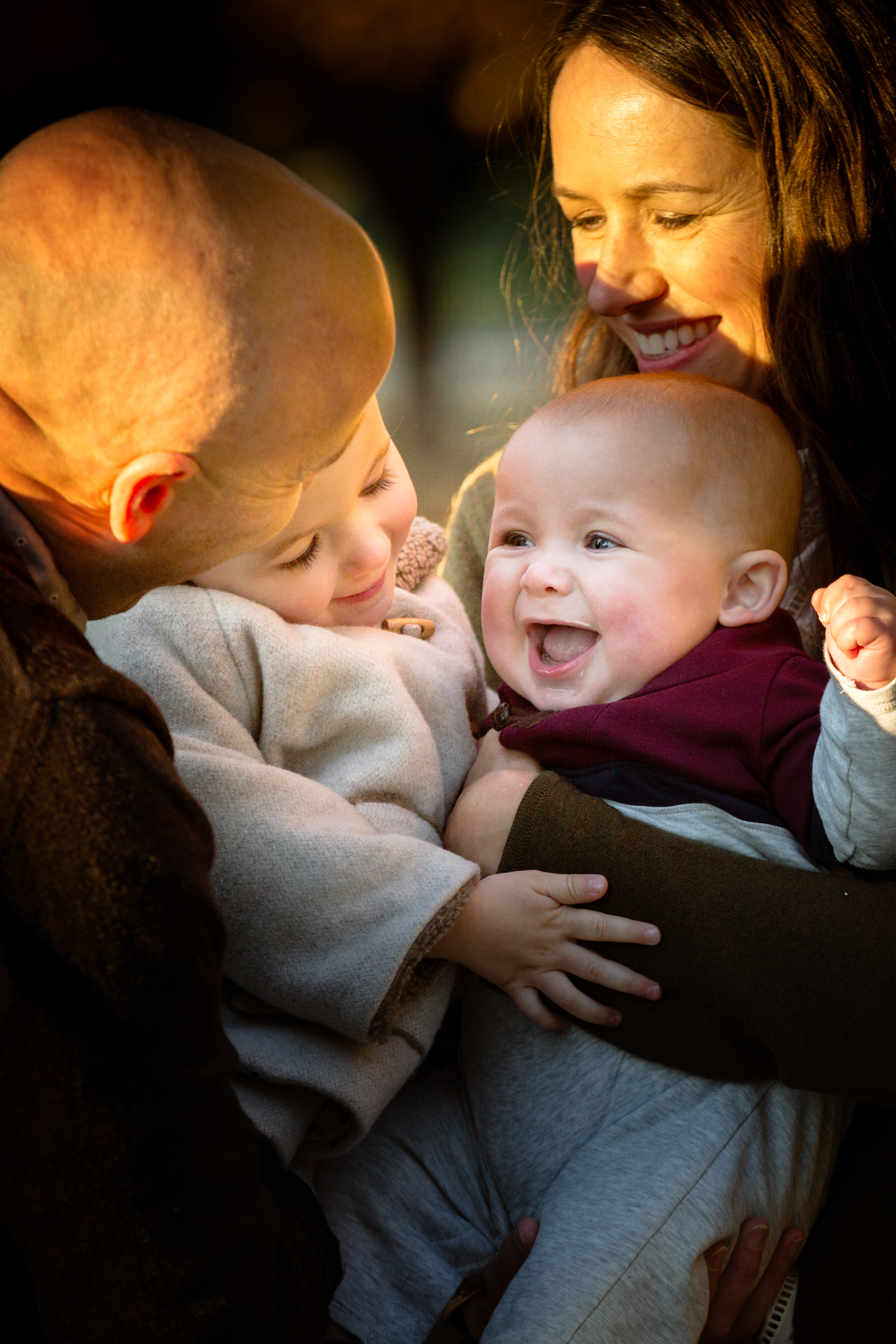 family of four snuggles together and baby son grins