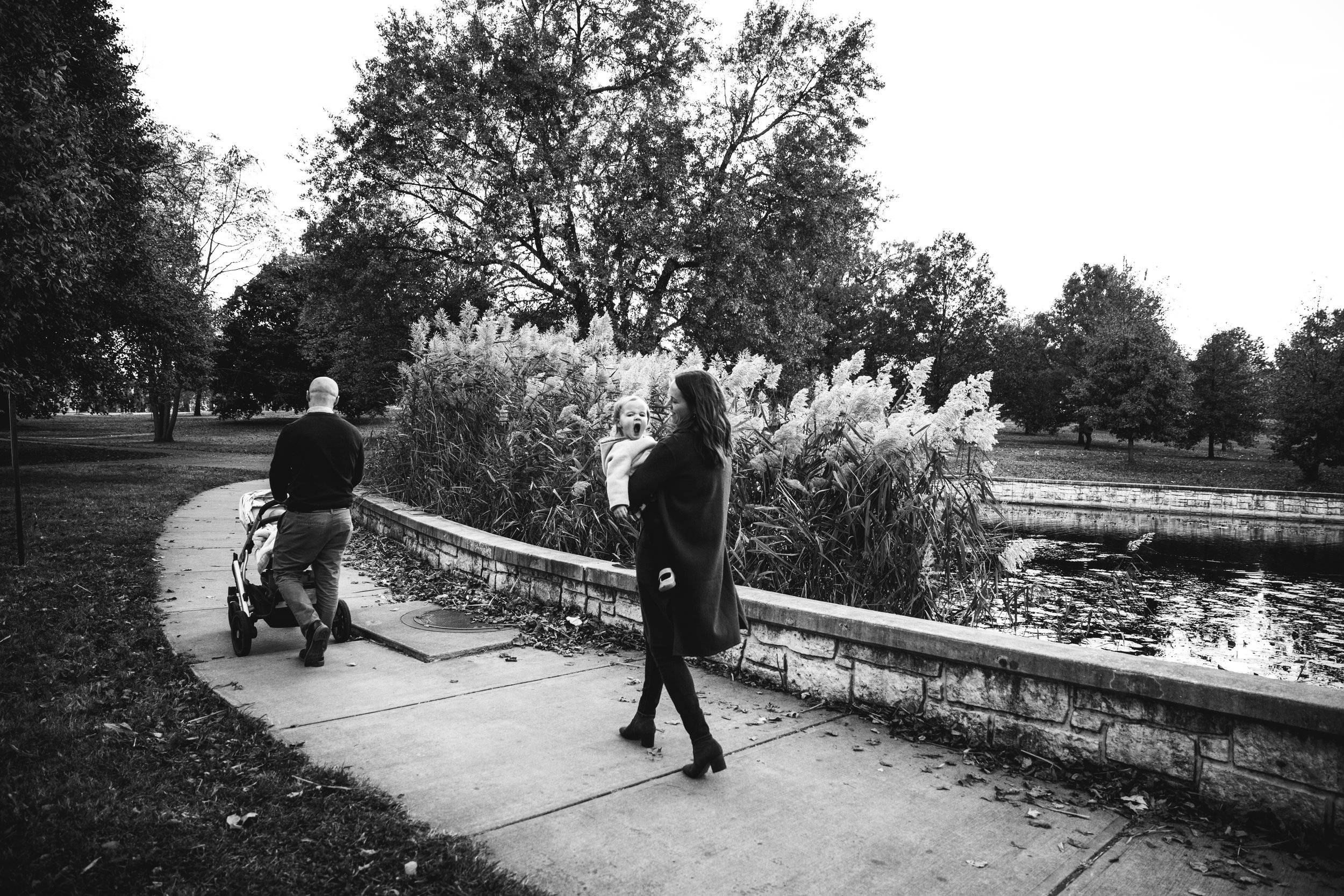 black and white photograph of family walking with stroller by park pond while mom holds daughter who yawns