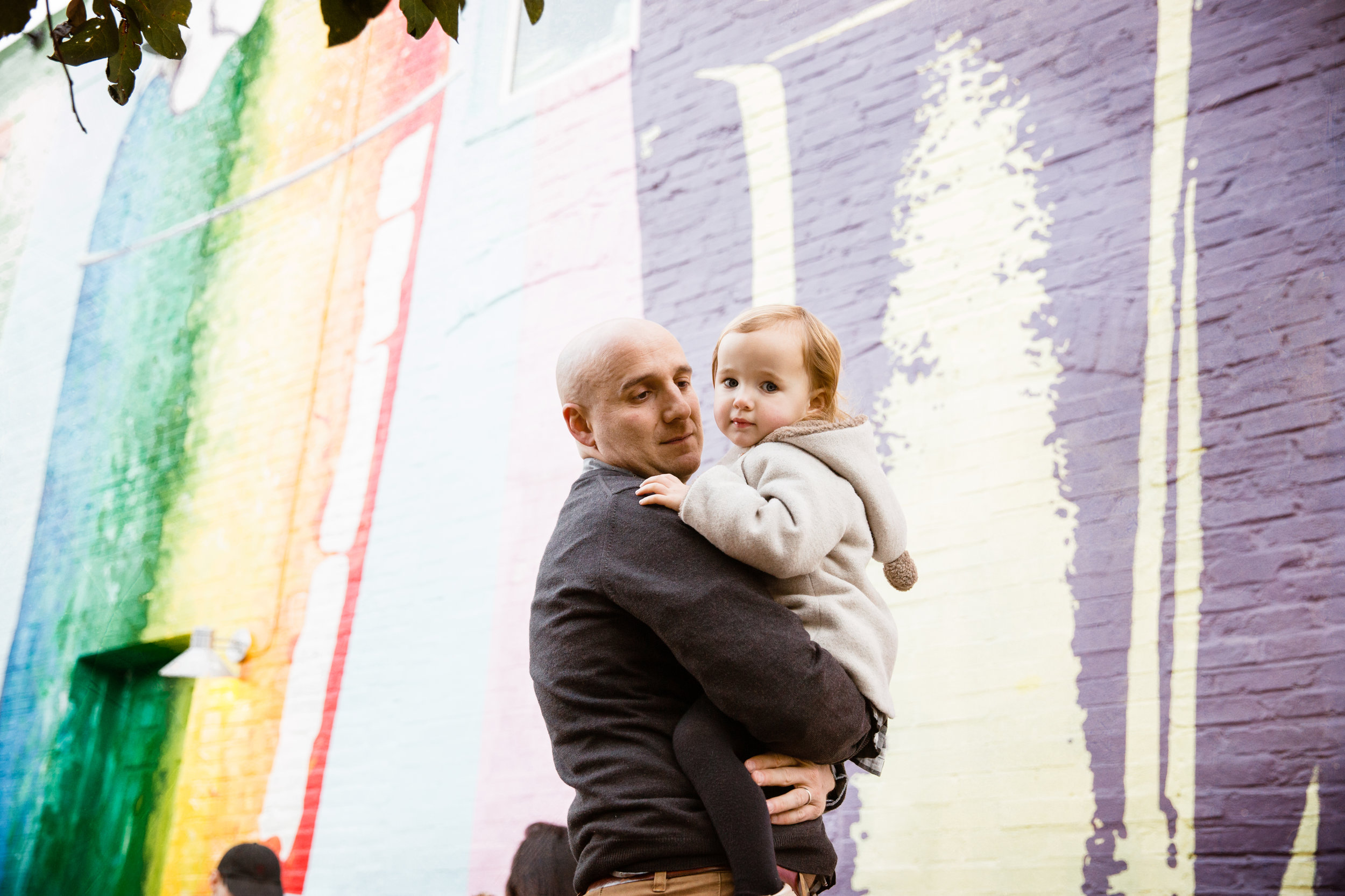 dad holds daughter in front of ice cream shop mural on the streets in the city