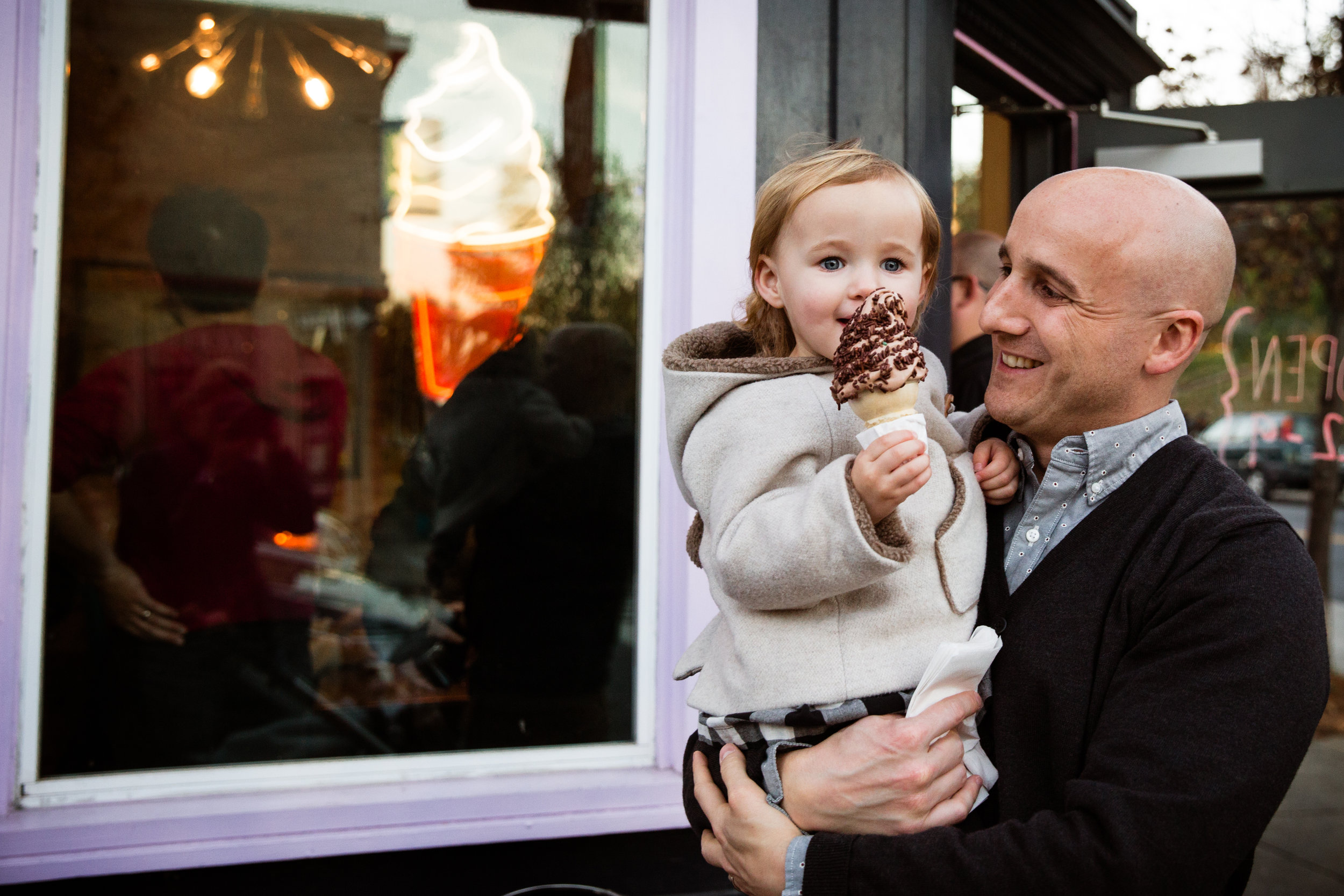 little girl in her father's arms proudly holds up ice cream cone she is eating