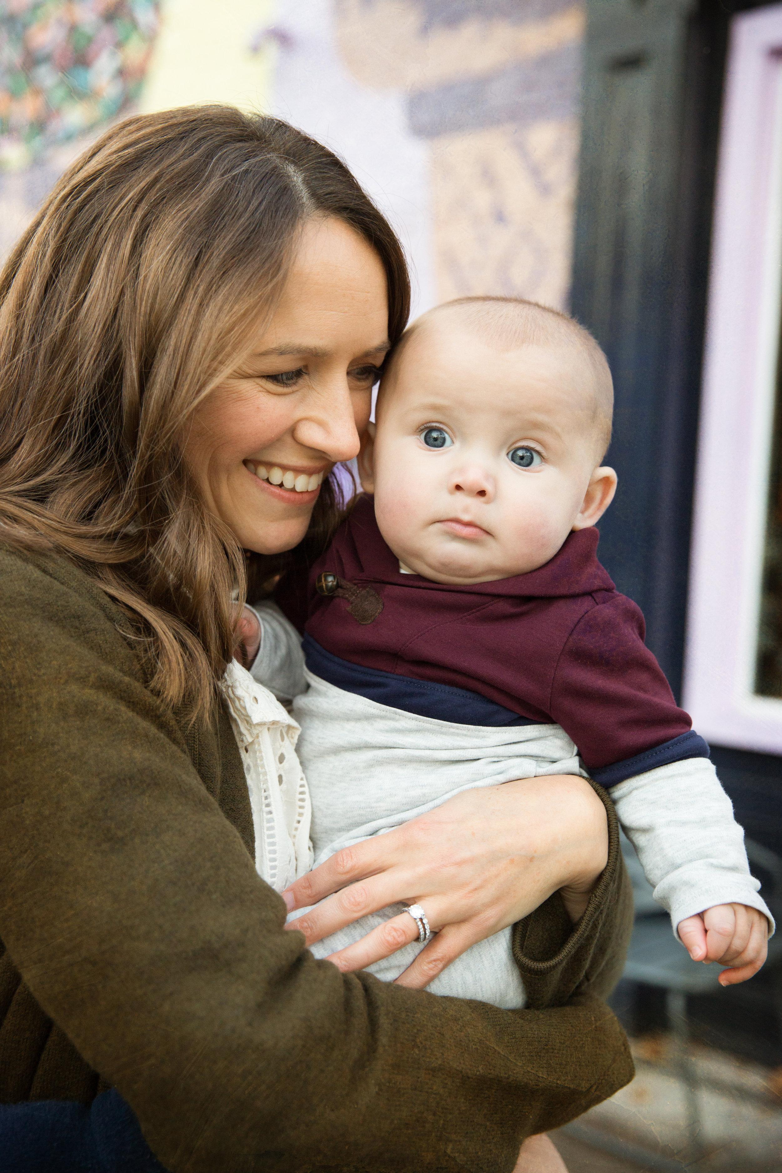 Mom snuggles cutest baby boy son on street outside a shop