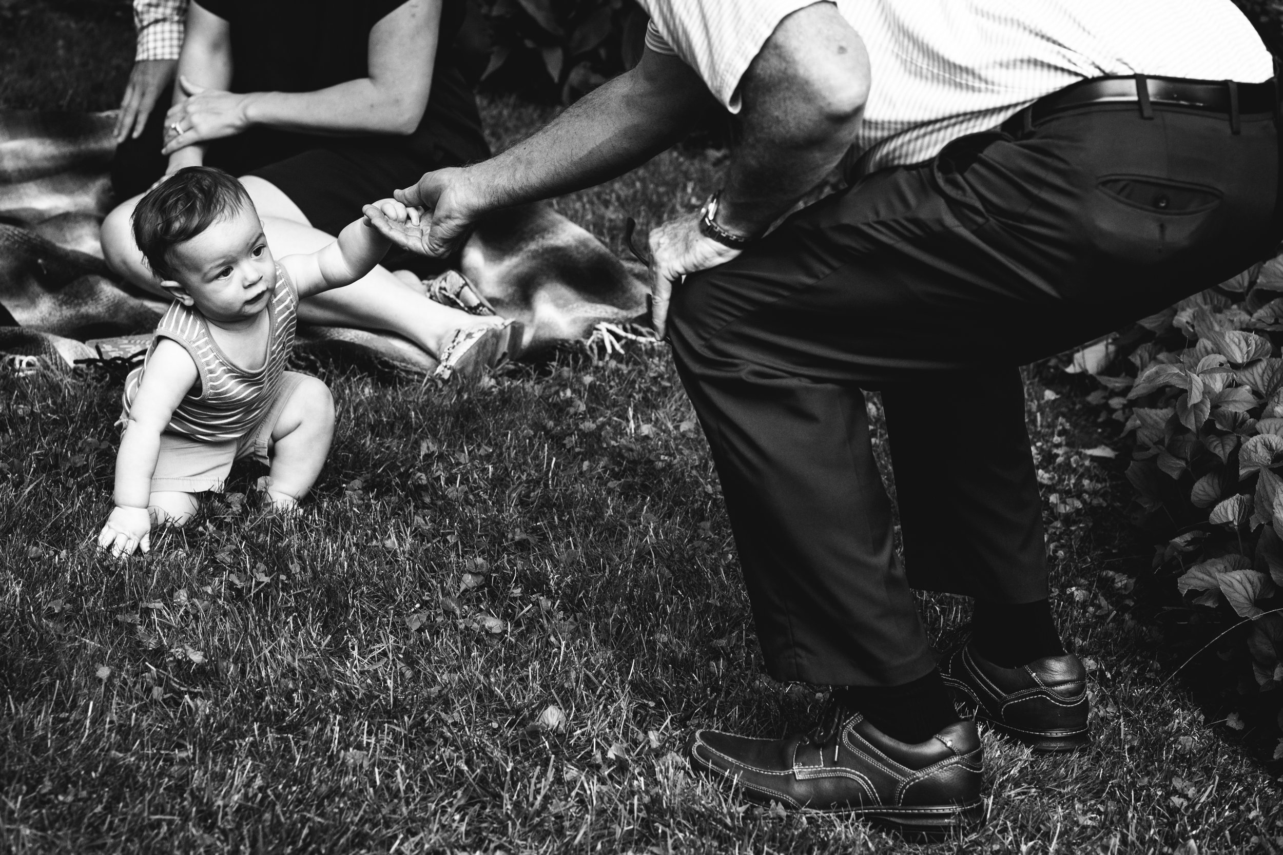 black and white photograph of father helping his son stand up to walk in the grass
