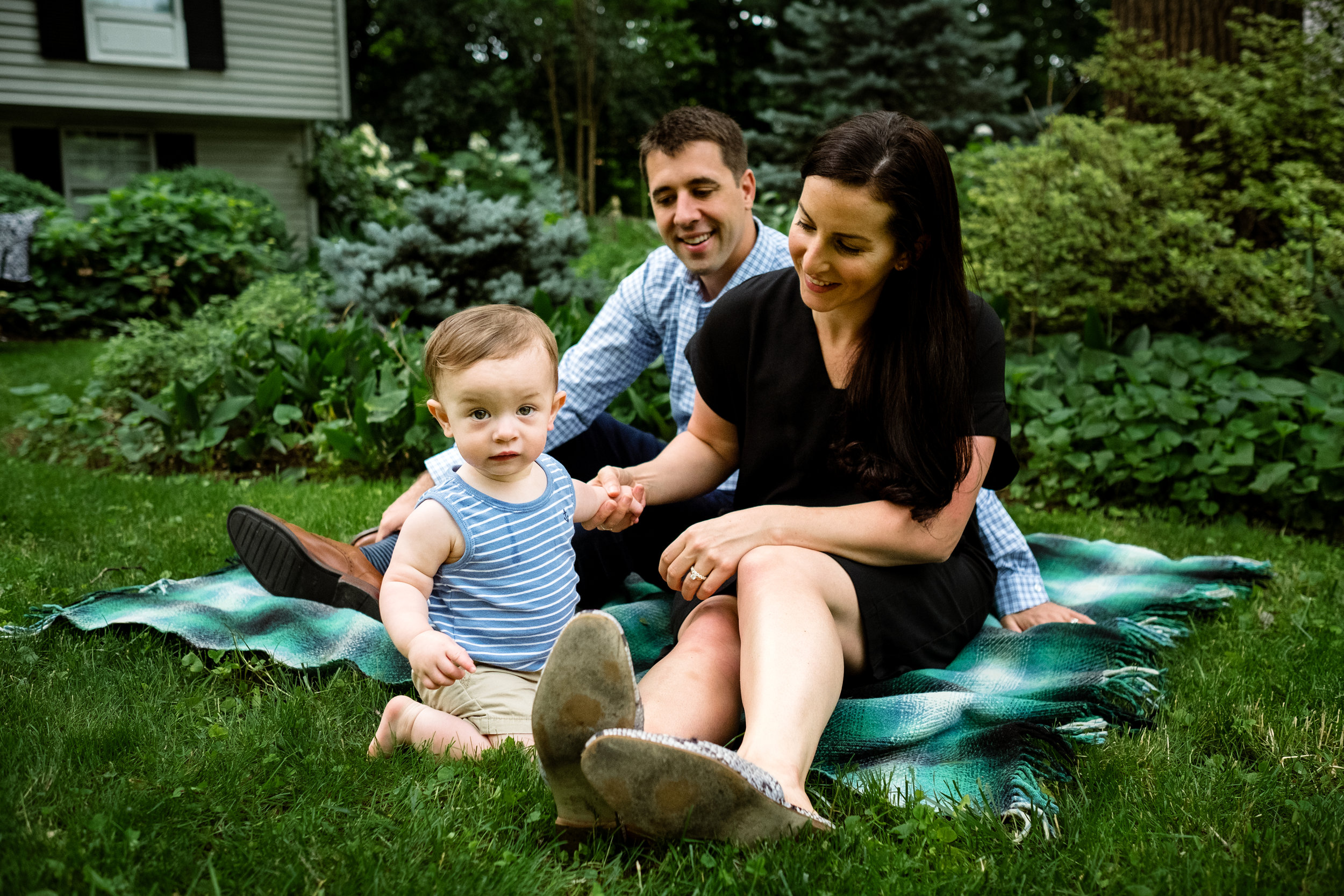 young family including parents and one year old boy sit on blanket in the grass
