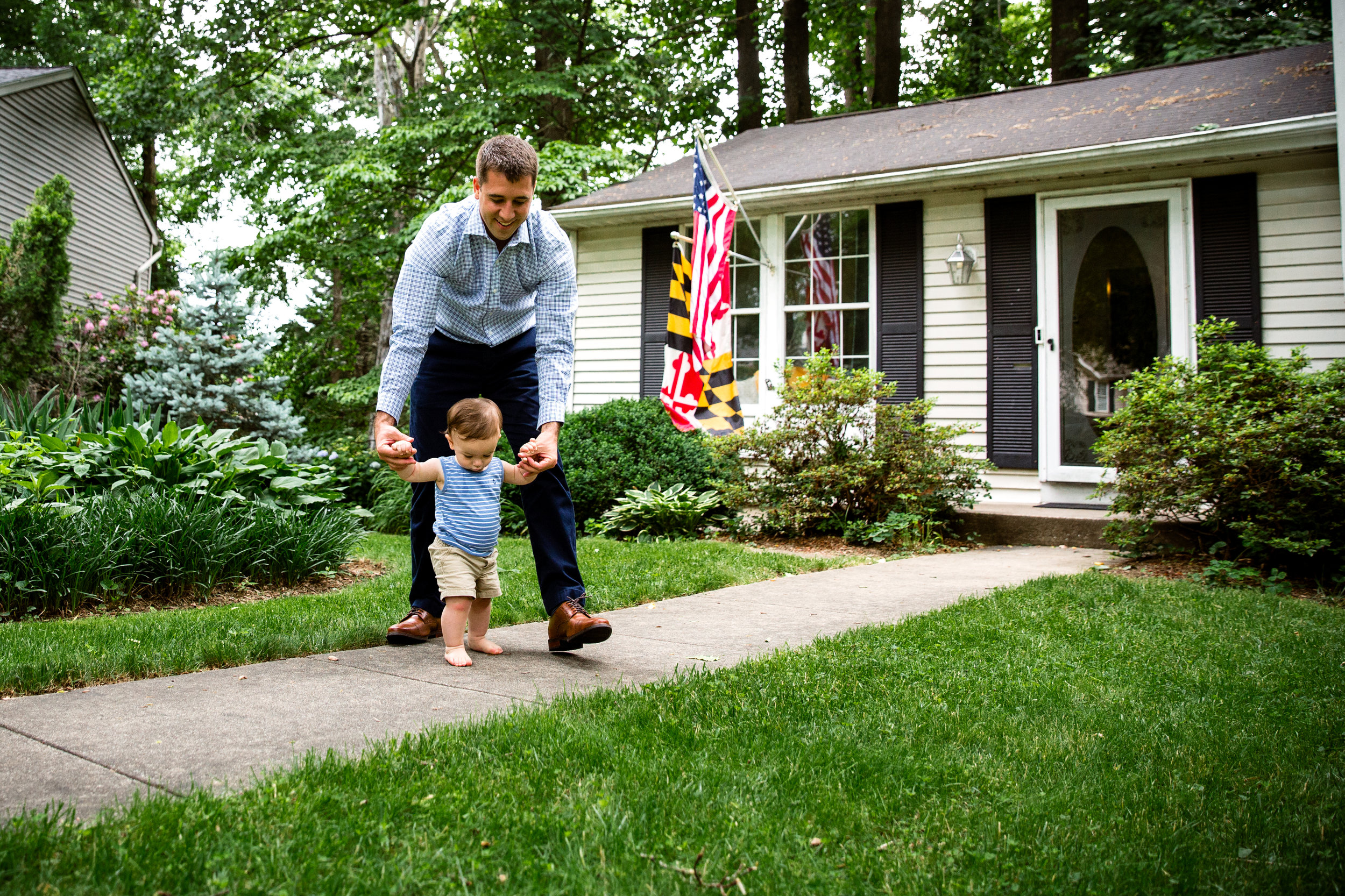 documentary family photograph of dad helping son walk outside grandparent's suburban home