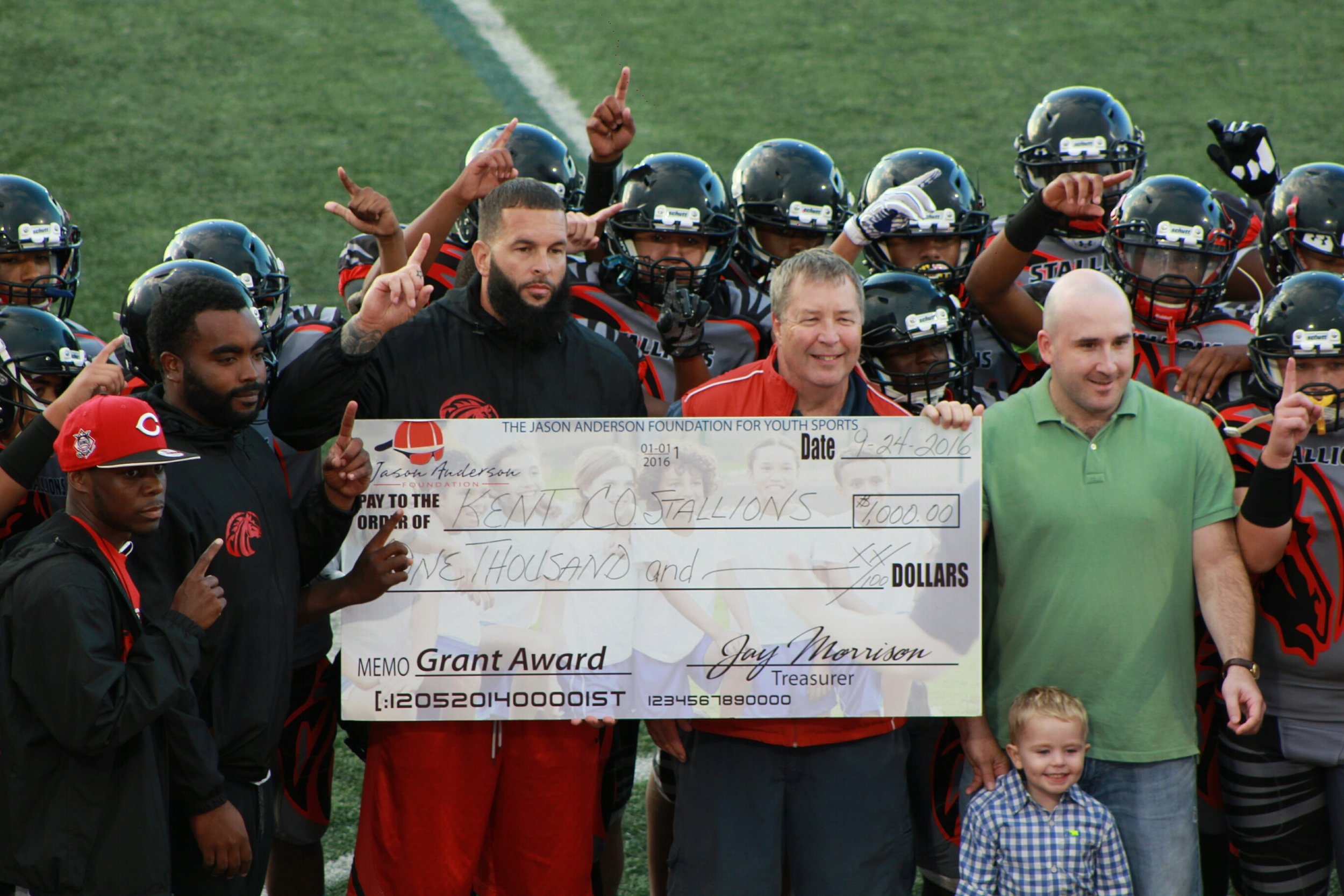 Marc Anderson, President of the foundation,  Andrew Schwab, Board Chair and Jason's son Ryan,  present a $1,000 check to the Kent County Stallions prior to a September 2016 game.