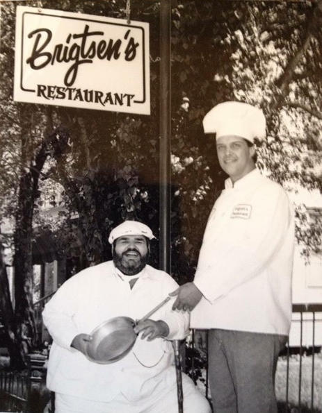 Chef Prudhomme and Chef Frank Brigtsen, passing the skillet outside of Brigtsen's Restaurant, 1986.    COURTESY OF FRANK BRIGTSEN