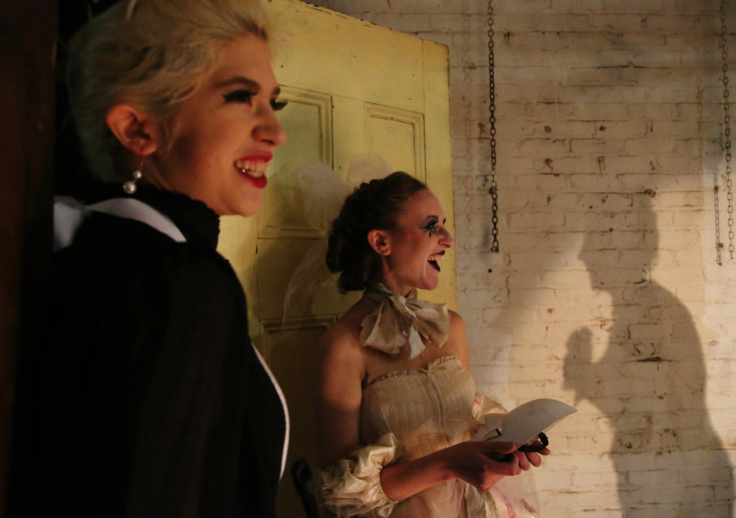 """Amy Brooks (whose shadow is shown right) talks to Burlesque Dancers Pearl Buttons (left) and Devora Darling (second from left) during the first dress rehearsal of the """"Wrathskellar Tales,"""" a production of the Burlesque Troupe, """"The Boston BeauTease,"""" on Oct. 19, 2016 in Cambridge, Mass.""""  It's [burlesque dancing] been such therapy for me, to be there, and to feel freer with my body, and to allow people to see things that I never let people see before, with lights on,"""" Brooks said, laughing.  Full story here."""