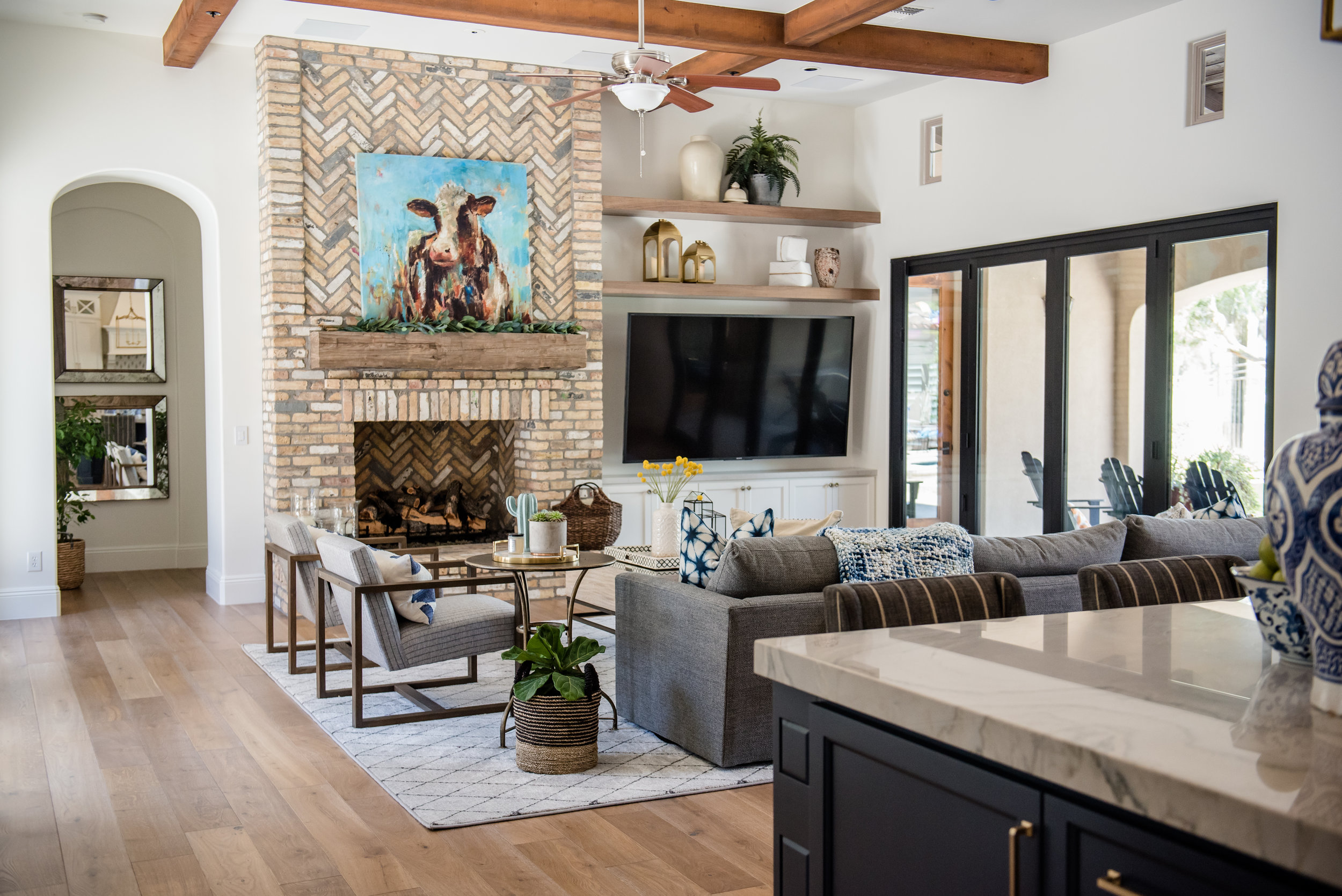 33+fireplace+brick+woodenchairs+art+brass+accessories+builtins+familyroom+rug.jpg