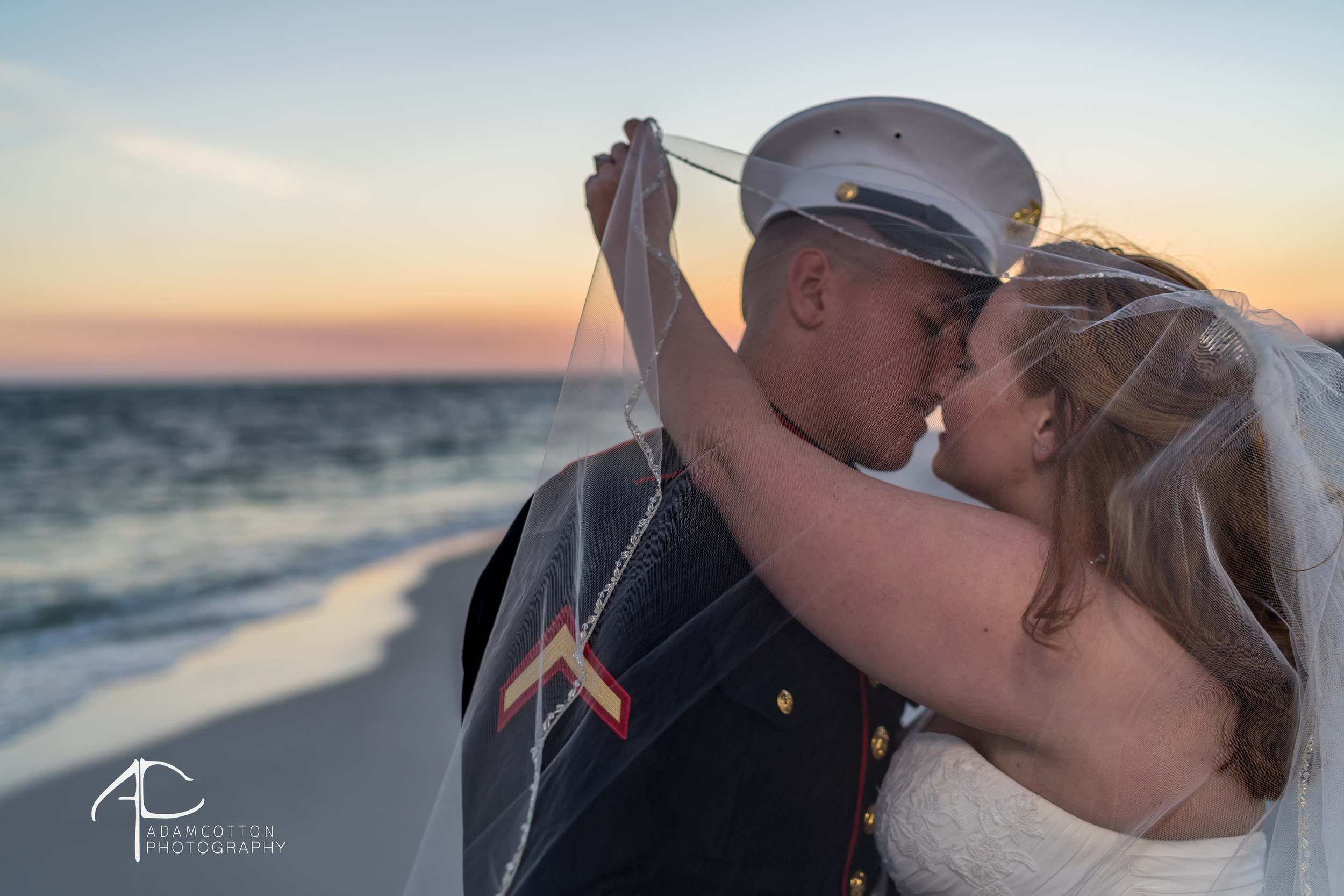image bride groom kissing under veil pensacola wedding sunset