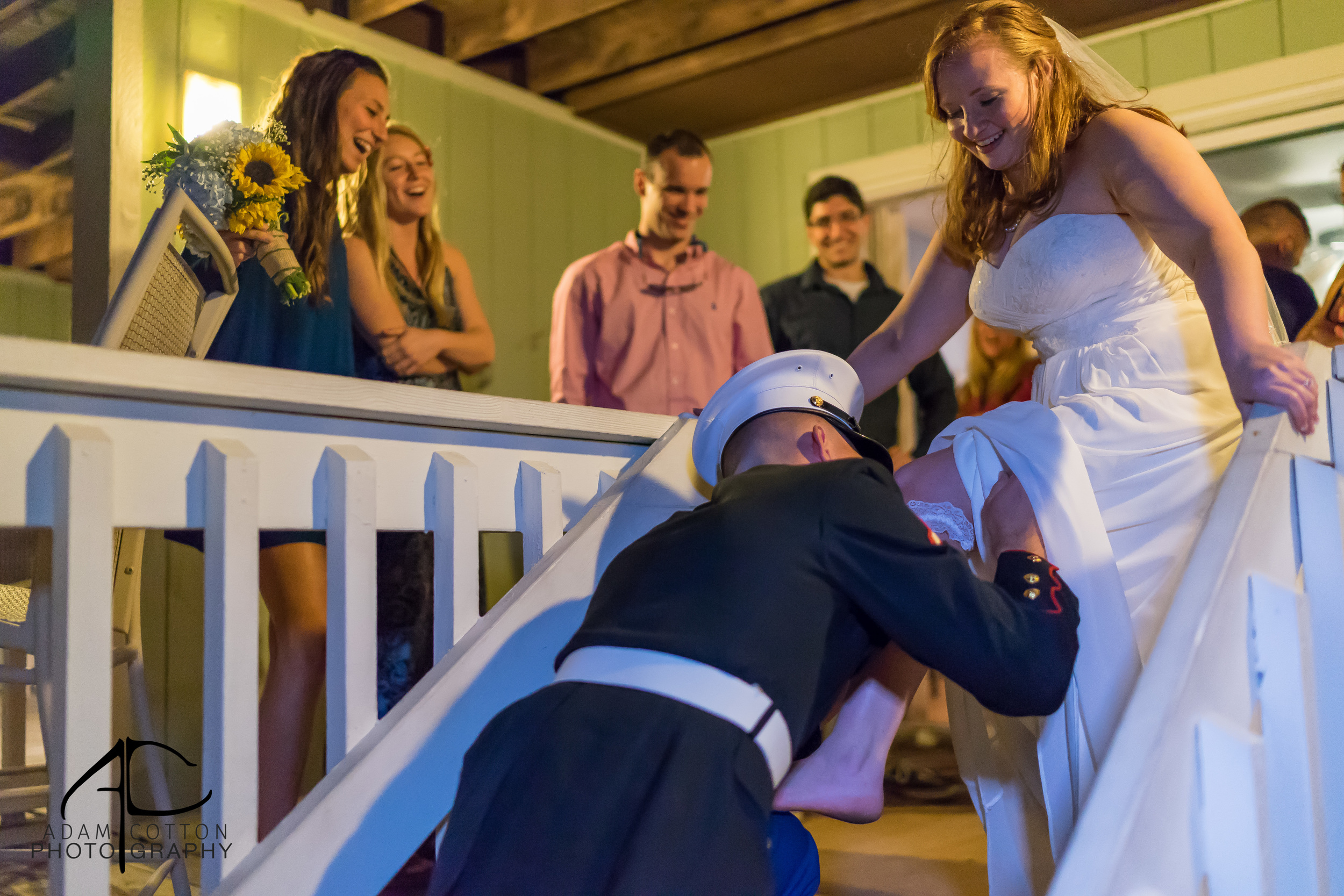 image of groom removing garter from bride pensacola florida wedding photographer adam cotton