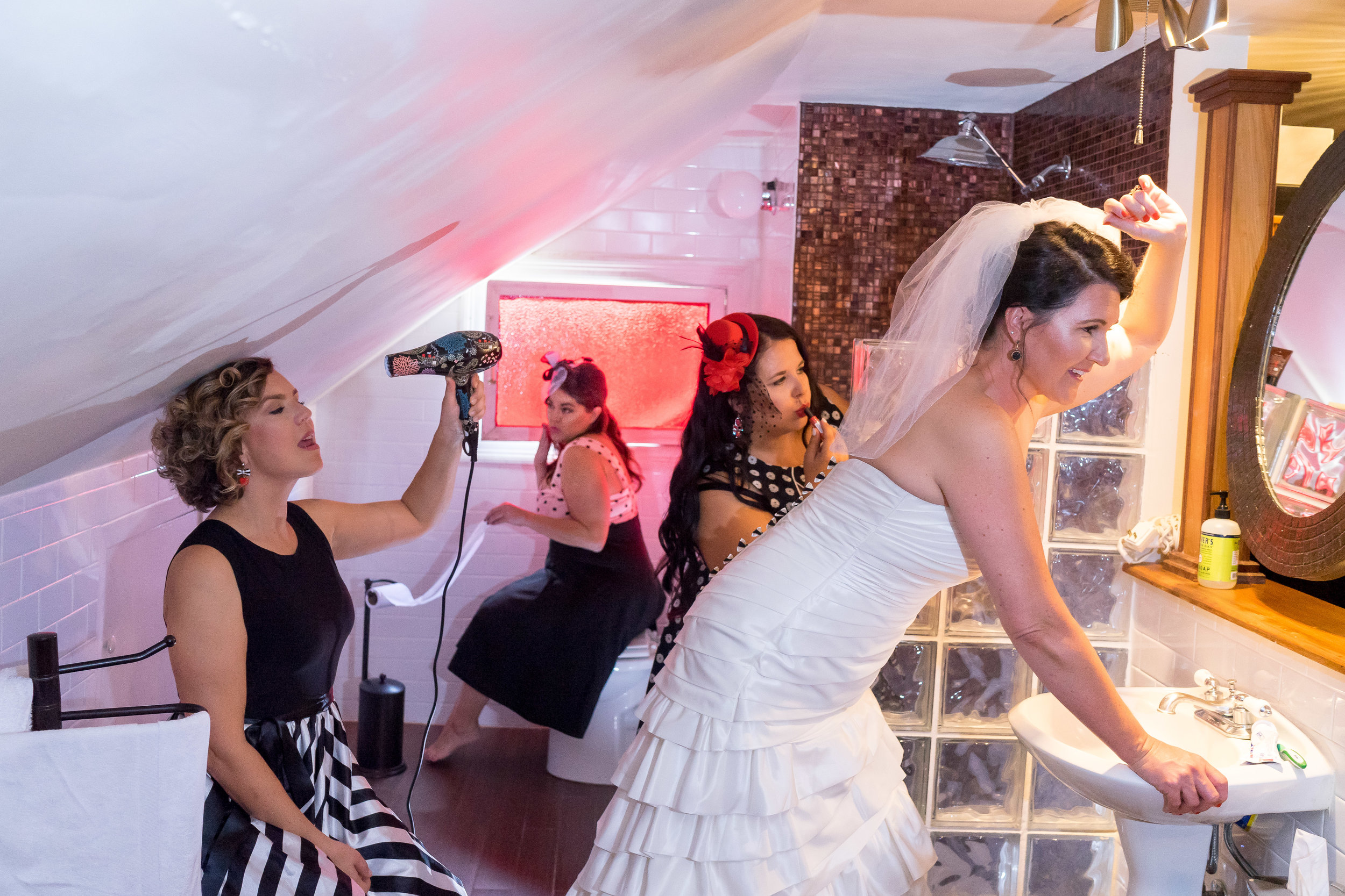candid image of bride and bridesmaids getting ready in bathroom commercial wedding photographer adam cotton